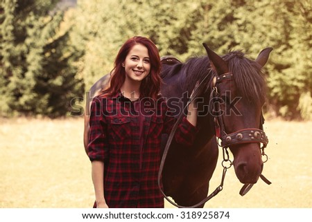 Redhead girl with horse in the forest  - stock photo