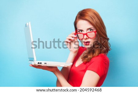 Redhead girl with laptop on blue background. - stock photo