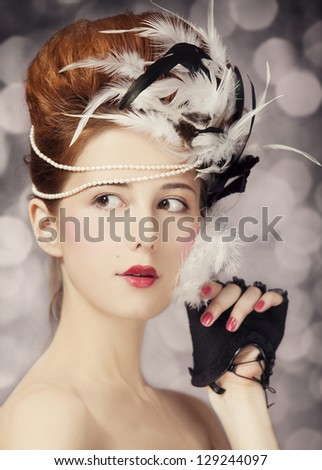 Redhead girl with Rococo hair style at vintage background. Photo in old style.