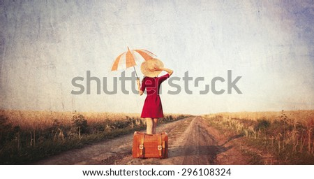 Redhead girl with suitcase and umbrella at countryside road - stock photo