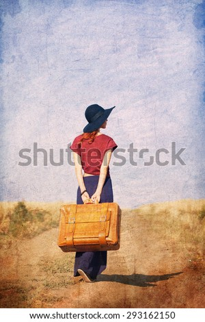 Redhead girl with suitcase at countryside road near wheat field. Photo in old color image style. - stock photo