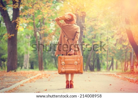 Redhead girl with suitcase in the autumn park. - stock photo