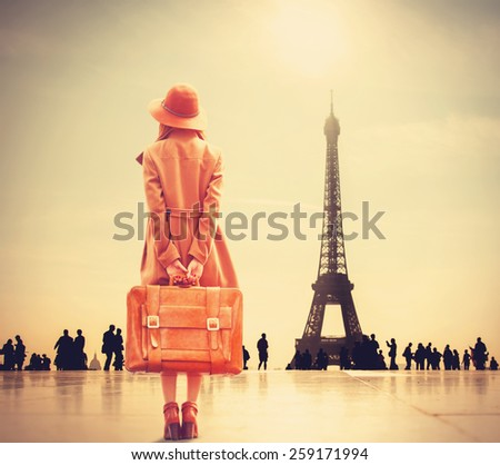 Redhead girl with suitcase on Eiffel tower background - stock photo