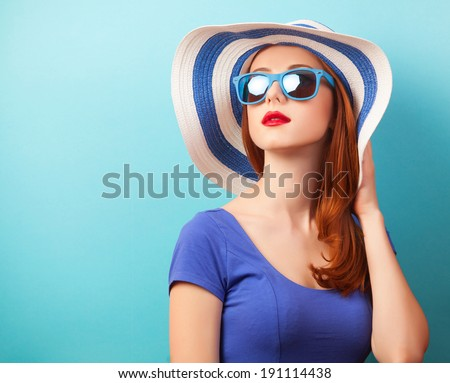 Redhead girl with sunglasses and hat on blue background. - stock photo