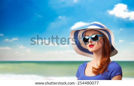 Redhead girl with sunglasses and hat on marine background.