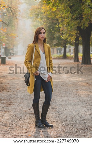 Redhead girl with yellow coat posing in a city park