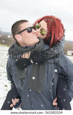 Redhead girlfriend lying on her boyfriend's back outdoors in the winter - stock photo