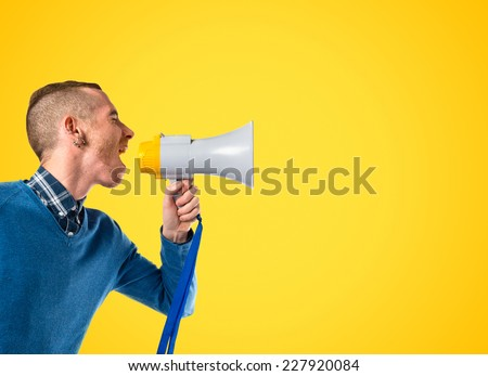 Redhead man shouting by megaphone over yellow background  - stock photo
