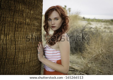 Redhead model posing in a paradise setting