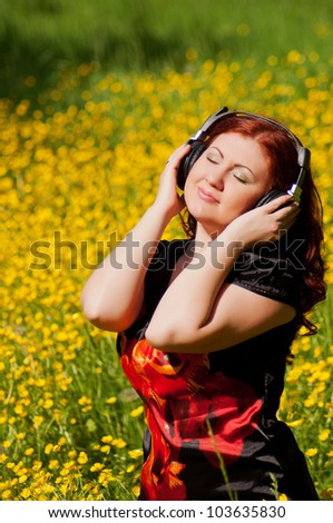 redhead pretty girl with headphones listening to music in nature in a field of flowers - stock photo