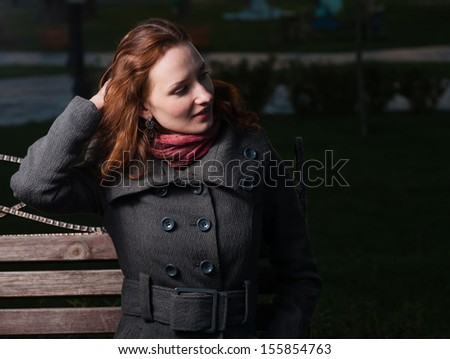redhead 20s women sitting on bench outdoor in autumn park, weared scarf and coat