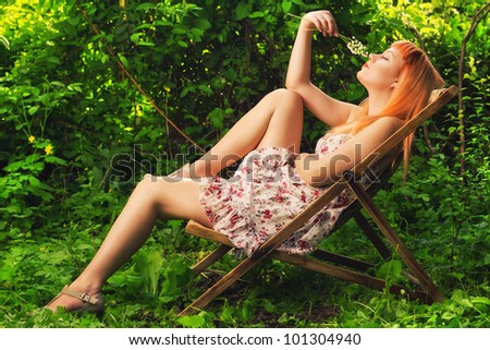 Redhead sitting in a lounge chair outdoors