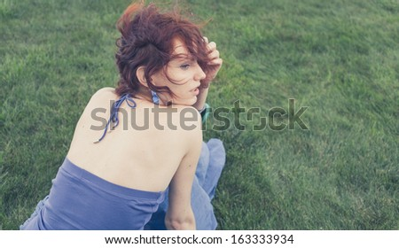 redhead sitting on grass, backview, toned image