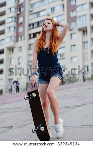 Redhead slim girl in jeans shorts and black t shirt posing with skateboard in urban sciene.