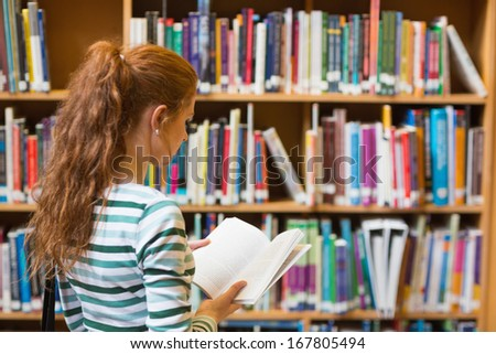 Redhead student reading book from shelf in library at the university