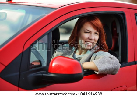 redhead stylish woman driving the red car