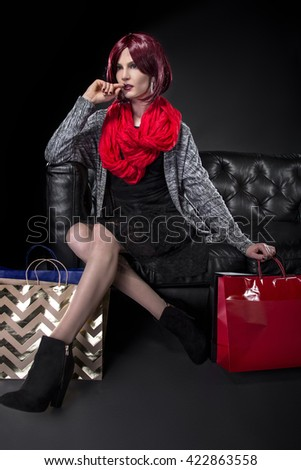 Redhead with Shopping Bags on a Black Leather Couch.  She is dressed in a red scarf.