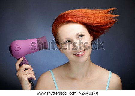 Redhead woman drying her hair