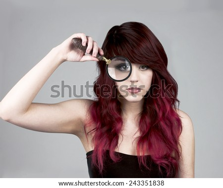 Redhead woman holding a magnifying glass - stock photo