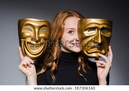 Redhead woman iwith masks in hypocrisy consept against grey background - stock photo