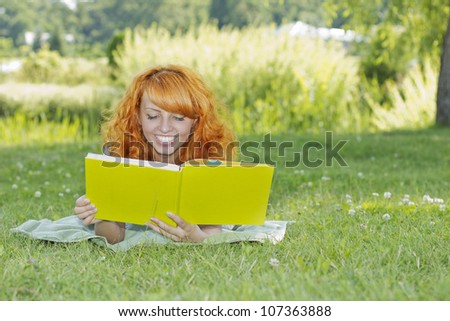 Redhead woman lies on green grass and reads green book, covers the face during spring / summer time . Happy smiling beautiful young university student studying lying down in grass.