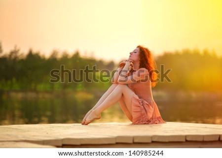 redhead woman near the river in sunny bright light - stock photo