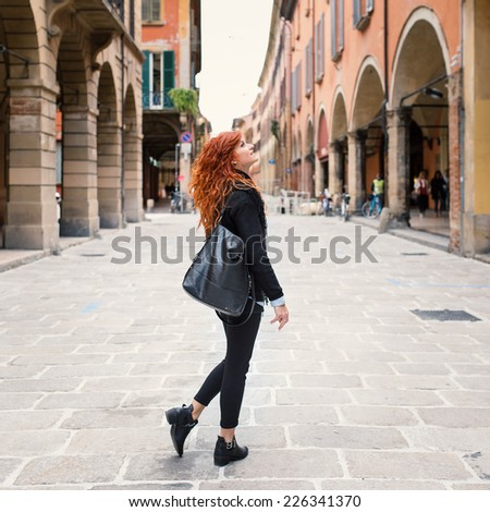 Redhead woman portrait walking in the street. - stock photo