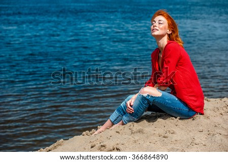 Redhead woman sitting comfortably and smiling, looks serene and free and enjoying a sunny day at the beach. - stock photo