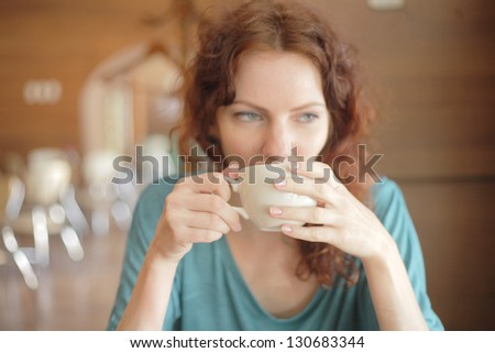 Redhead woman with curly hair drinking coffee from a cup shallow depth of field