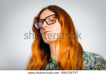 Redhead young woman looking condescendingly, isolated close-up