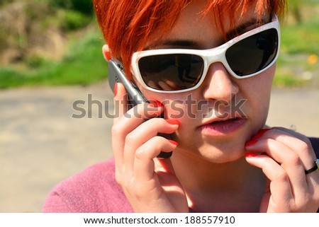 redhead young woman talking on cellphone - stock photo