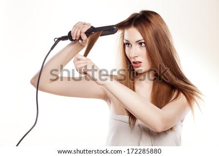 redheaded girl straightens the hair using a hair straightener - stock photo