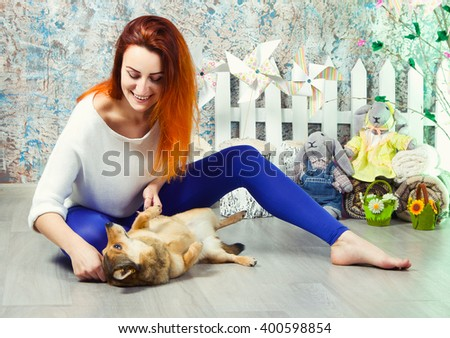 redheaded happy girl plays with a dog - stock photo