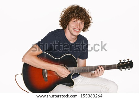 Redheaded male musician with his acoustic guitar over white background - stock photo