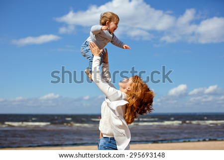 Redheaded mom in jeans and a white sweater throws up his young son against the sea and clouds - stock photo