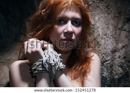 redheaded nude woman bondage in catacomb - stock photo