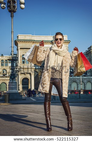 Rediscovering things everybody love in Milan. Full length portrait of happy young tourist woman with shopping bags near Galleria Vittorio Emanuele II in Milan, Italy rejoicing