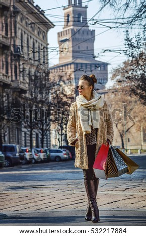 Rediscovering things everybody love in Milan. Full length portrait of trendy woman with shopping bags near Sforza Castle in Milan, Italy looking into the distance