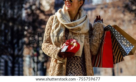 Rediscovering things everybody love in Milan. happy young woman with shopping bags and Christmas gift near Sforza Castle in Milan, Italy looking into the distance