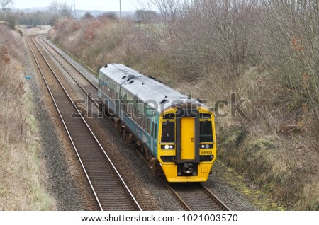 REDNAL, UK - MARCH 8: An Arriva operated class 158 DMU outer suburban commuter train passes Rednal race circuit on route to Hereford on March 8, 2017 in Rednal
