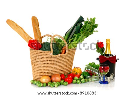Reed shopping bag with fresh bio vegetables, bread, champagne on reflective surface, studio shot, white background. - stock photo