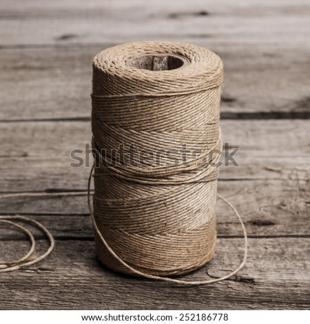 reel of durable thread on the wooden table - stock photo