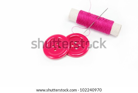 Reel of thread with a needle and buttons on a white background.