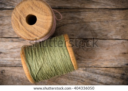 Reel pink with green yarn left side on wood background - stock photo
