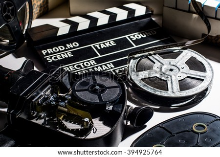 Reel with film and cinema clap. Film boxes. Open the lid cameras - stock photo