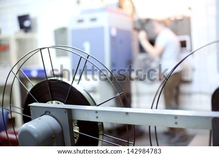 Reels for videotape in room of movie theater and operator at background. Shallow depth of field.