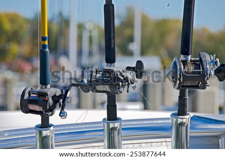 reels on fishing rods in chrome holders on a boat - stock photo