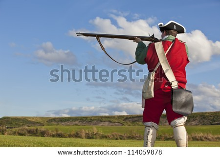 Reenactor in 18th century British army infantry Redcoat uniform aiming his rifle - stock photo