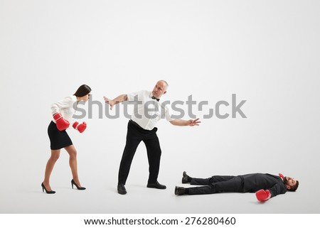 referee holding angry businesswoman in boxer gloves and counting down to knocked out businessman over light grey background - stock photo