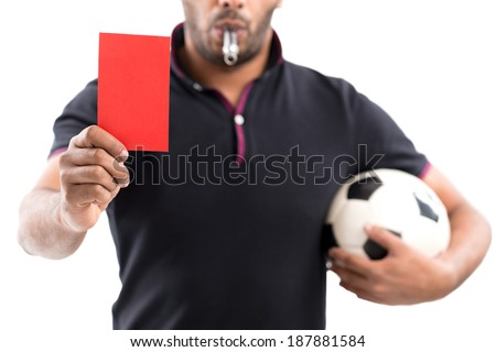Referee holding ball and showing a red card - stock photo